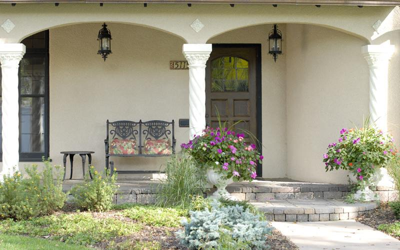 A stucco retouch on a graceful front porch with walkway and plantings